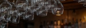 Wine Glasses hanging from rock over bar